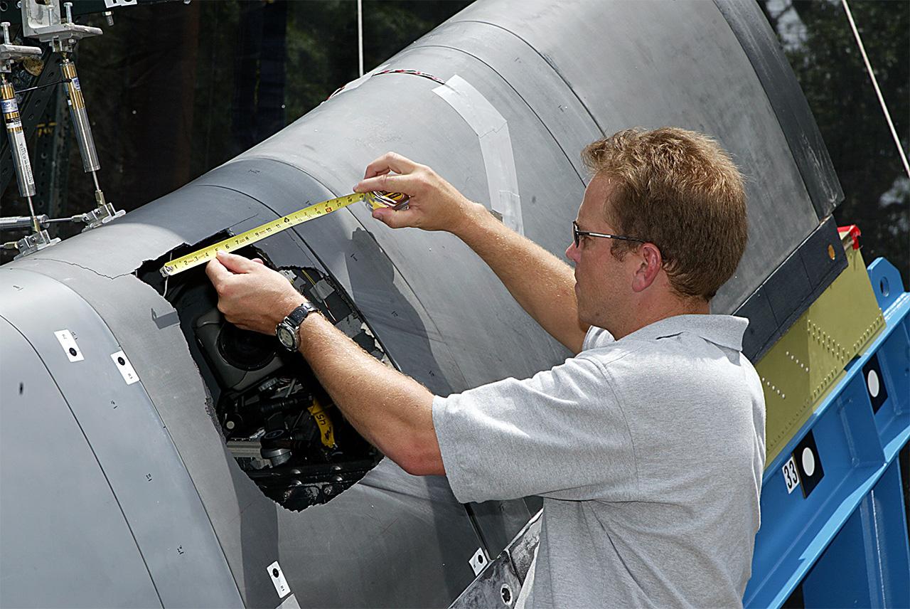 Dan Bell del comitato di indagine CAIB misura il danno su un modello del bordo di attacco dell'ala del Columbia in un test a terra